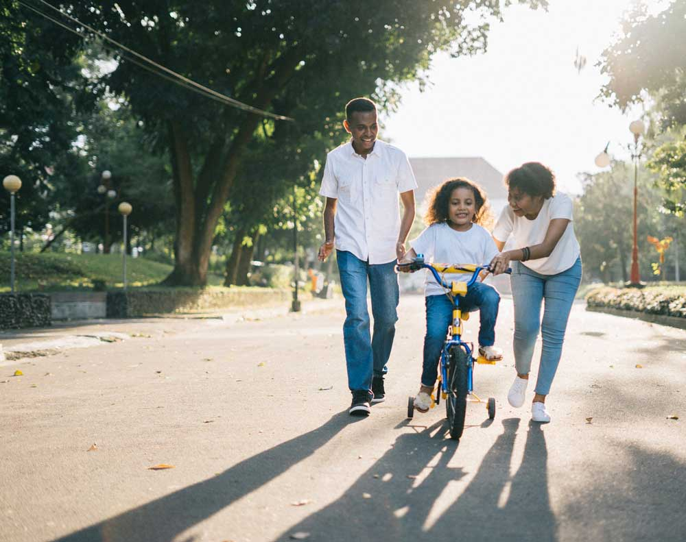 man-standing-beside-his-wife-teaching-their-child-how-to-1128318